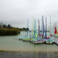 kleurrijke bootjes op regenachtige dag aan het meer van Annecy